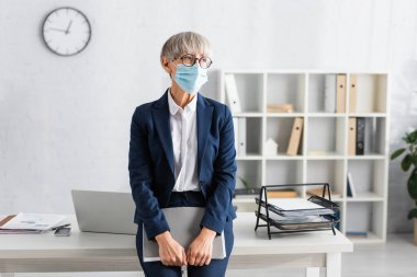 Mature team leader in glasses and medical mask holding folder while standing near workplace stock vector