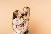 cheerful blonde mother hugging and looking at happy daughter isolated on beige