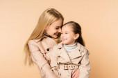 joyful blonde mother hugging happy daughter in trench coat isolated on beige