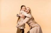happy kid embracing amazed blonde mother isolated on beige