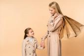 boldog anya papírzacskók fogják egymás kezét gyerek elszigetelt bézs