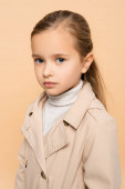 kid in trench coat looking at camera isolated on beige