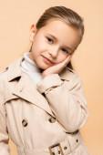 potěšené dítě v trenč kabát při pohledu na kameru izolované na béžové