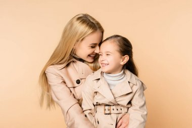 Joyful blonde mother hugging happy daughter in trench coat isolated on beige stock vector