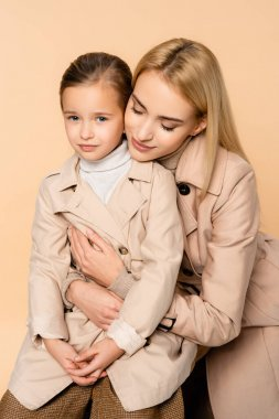 Caring mother hugging daughter in trench coat isolated on beige stock vector