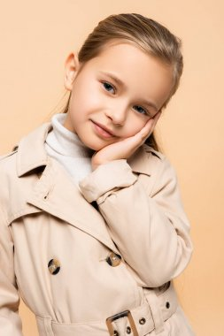 Pleased child in trench coat looking at camera isolated on beige stock vector