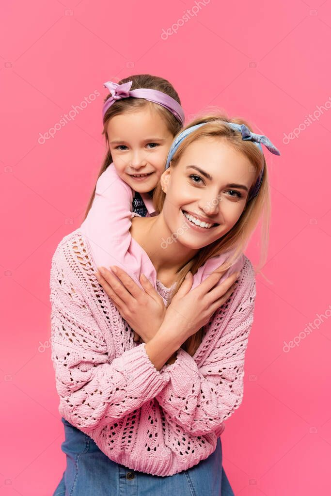 Cheerful kid hugging happy mother isolated on pink stock vector