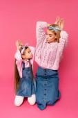 anya és lánya, hogy nyuszi fülek kézzel, és nézik egymást rózsaszín