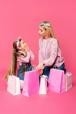 Shocked mother and daughter looking at each other near shopping bags on pink stock vector