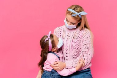 Mother and daughter in medical masks hugging and looking at each other isolated on pink stock vector
