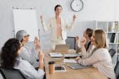 Lächelnder Teamchef, der mit geballten Fäusten neben multikulturellen Geschäftsfrauen im verschwommenen Vordergrund steht
