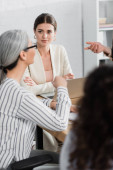 team leader looking at asian businesswoman during meeting in office