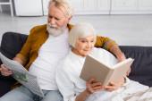 Usmívající se starší pár čtení knihy a novinky na gauči doma