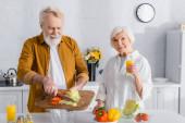 Starší žena drží sklenici pomerančové šťávy v blízkosti manžela nalévání zeleniny v misce v kuchyni