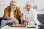 Idős pár sakkozik újság és távirányító közelében elmosódott előtérben