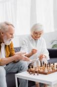 Mosolygó idős nő ül közel sakk a fedélzeten, és a férj mutató kézzel elmosódott előtérben