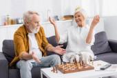 Idősebb férfi mutató kezét a sakk vaddisznók közelében mosolygó feleség kanapén