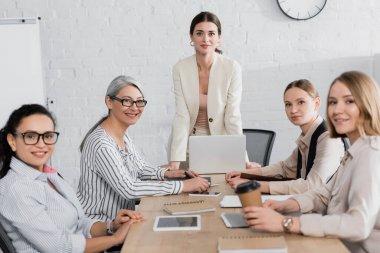 Team leader standing near happy multiethnic businesswomen during meeting in office stock vector