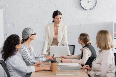 Happy team leader standing near multiethnic businesswomen during meeting in office stock vector