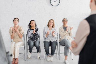 Happy multicultural businesswomen applauding to speaker during seminar stock vector