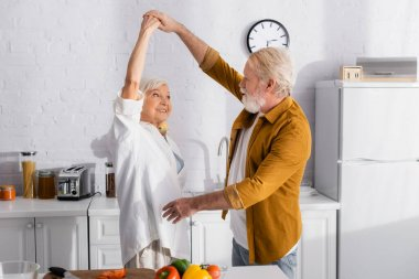 Cheerful senior couple dancing near fresh vegetables on kitchen table