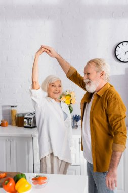Smiling elderly man dancing with fife near vegetables n blurred foreground on kitchen table