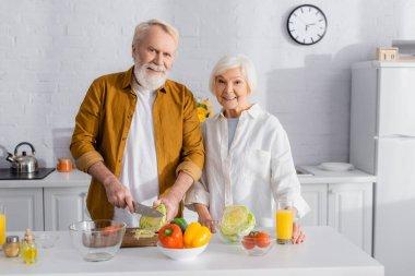 Gülümseyen yaşlı kadın kocasının yanında duruyor mutfakta lahana ve portakal suyu kesiyor.
