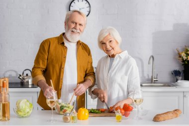 Smiling elderly couple cooking fresh salad near wine and baguette in kitchen stock vector