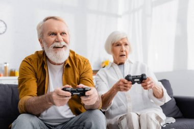 KYIV, UKRAINE - DECEMBER 17, 2020: Cheerful senior man playing video game near upset wife on blurred background stock vector