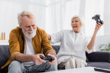 KYIV, UKRAINE - DECEMBER 17, 2020: Senior man with joystick sitting near wife and remote controller on blurred foreground stock vector