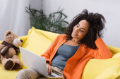 vidám afro-amerikai szabadúszó nézi laptop otthon