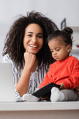 smiling african american mother looking at camera near toddler daughter on desk