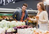 Usmívající se muž stojí v blízkosti nákupního košíku a přítelkyně s cibulí na rozmazané popředí v supermarketu