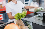 Cropped view of lettuce in hand of cashier in supermarket on blurred background