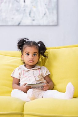 Toddler african american girl holding smartphone while sitting on sofa stock vector