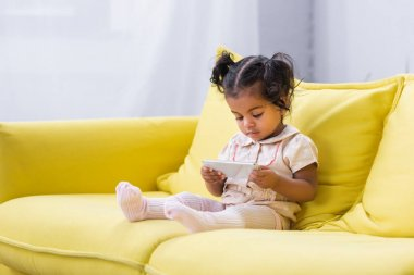 Toddler african american girl using smartphone while sitting on couch stock vector