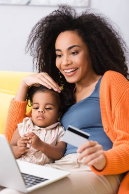 Smiling african american mother holding credit card and using laptop near toddler daughter in living room stock vector