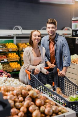 Smiling couple standing near shopping cart and vegetables in supermarket stock vector