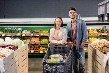 Young couple standing near shopping trolley and vegetables in supermarket stock vector