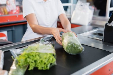 Cropped view of cashier taking lettuce from supermarket checkout stock vector