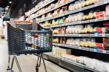 Shopping cart near packages on shelves in supermarket stock vector