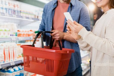 Cropped view of woman using smartphone near boyfriend putting bottle in shopping basket stock vector