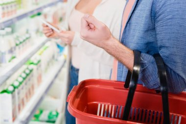 Cropped view of man holding shopping basket near girlfriend on blurred background in supermarket stock vector