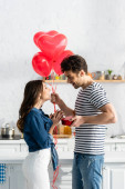 side view of happy man holding heart-shaped balloons and gift box near smiling girlfriend
