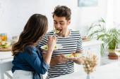 žena drží talíř a krmení přítel s salátem