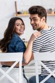 veselý muž a žena objímání a posezení na židlích