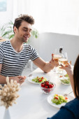 veselý muž toasting sklenice vína s ženou u oběda na stole