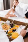 Muž drží podnos se snídaní s pomerančovou šťávou a ovoce v blízkosti přítelkyně na hotelovém lůžku na rozmazaném pozadí