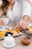 Vágott kilátás férfi vesz narancs szelet közelében élelmiszer és barátnője homályos háttér szálloda