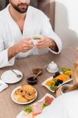 Vágott kilátás férfi fürdőköpenyben kezében csésze kávét közel ízletes reggeli az asztalon és barátnője elmosódott előtérben a szállodában